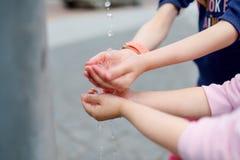 Δύο αδελφές που έχουν τη διασκέδαση με την πηγή πόσιμου νερού την ηλιόλουστη θερινή ημέρα Στοκ εικόνα με δικαίωμα ελεύθερης χρήσης