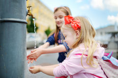 Δύο αδελφές που έχουν τη διασκέδαση με την πηγή πόσιμου νερού την ηλιόλουστη θερινή ημέρα Στοκ Φωτογραφίες
