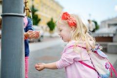 Δύο αδελφές που έχουν τη διασκέδαση με την πηγή πόσιμου νερού την ηλιόλουστη θερινή ημέρα Στοκ εικόνες με δικαίωμα ελεύθερης χρήσης