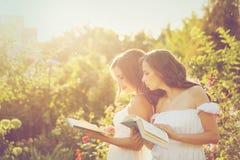Δύο αδελφές που διαβάζουν τα βιβλία Στοκ Φωτογραφίες