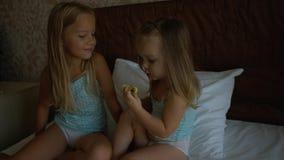 Δύο αδελφές που κάθονται στο κρεβάτι και που τρώνε το μήλο Στοκ Εικόνα
