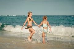 Δύο αδελφές που καταβρέχουν στην παραλία Στοκ εικόνες με δικαίωμα ελεύθερης χρήσης