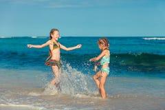 Δύο αδελφές που καταβρέχουν στην παραλία Στοκ Εικόνες
