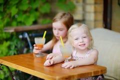 Δύο αδελφές που πίνουν το χυμό στον υπαίθριο καφέ Στοκ φωτογραφία με δικαίωμα ελεύθερης χρήσης