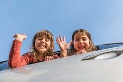 Δύο αδελφές που πηγαίνουν στις διακοπές και που κυματίζουν από μέσα από το αυτοκίνητο στοκ εικόνες