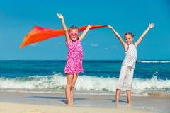 Δύο αδελφές που στέκονται στην παραλία και που σηκώνουν τα χέρια του Στοκ φωτογραφία με δικαίωμα ελεύθερης χρήσης