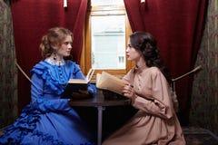 Δύο αδελφές στα αναδρομικά βιβλία ανάγνωσης φορεμάτων στο διαμέρισμα τραίνων Στοκ Φωτογραφία