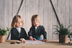 Δύο αδελφοί παιδιών που σύρουν μαζί στο σπίτι Ευτυχείς αμφιθαλείς που ξοδεύουν το χρόνο από κοινού Στοκ Εικόνες