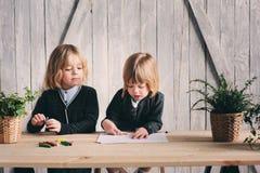 Δύο αδελφοί παιδιών που σύρουν μαζί στο σπίτι Ευτυχείς αμφιθαλείς που ξοδεύουν το χρόνο από κοινού Στοκ Φωτογραφία