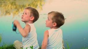 Δύο αδελφοί που αλιεύουν υπαίθρια Δύο μικρά ψάρια σύλληψης παιδιών σε μια λίμνη στο dacha Η όμορφη λίμνη το καλοκαίρι απόθεμα βίντεο