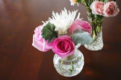 Δύο βάζα κρυστάλλου με τα μικροσκοπικά λουλούδια στον ξύλινο πίνακα στοκ εικόνες
