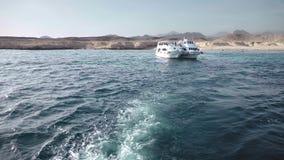 Δύο βάρκες που δένονται σε ένα εγκαταλειμμένο νησί στα πλαίσια των δύσκολων βουνών Σε ένα κρύσταλλο - σαφής ωκεανός φιλμ μικρού μήκους