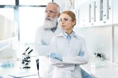 Δύο βέβαιοι επιστήμονες στα άσπρα παλτά και προστατευτικά δίοπτρα που κοιτάζουν μακριά και που θέτουν Στοκ Εικόνες