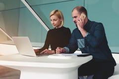 Δύο βέβαιοι επιχειρησιακοί εργαζόμενοι που χρησιμοποιούν το τηλέφωνο καθαρός-βιβλίων και κυττάρων για την ανάπτυξη του κοινού προ Στοκ Εικόνα