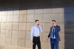 Δύο βέβαιοι νεαροί άνδρες, επιχειρηματίες, σπουδαστές που μιλούν στο phon στοκ φωτογραφία με δικαίωμα ελεύθερης χρήσης