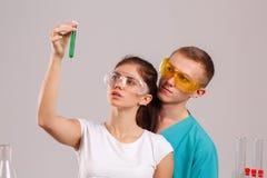 Δύο βοηθοί κρατούν στα χέρια τους και εξετάζουν μια μικρή φιάλη γυαλιού με ένα πράσινο υγρό στοκ εικόνα με δικαίωμα ελεύθερης χρήσης