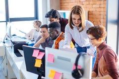 Δύο βοηθοί που βοηθούν τα νέα employeers που λειτουργούν με τον υπολογιστή και το lap-top στοκ εικόνες