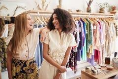 Δύο βοηθοί πωλήσεων θηλυκών που εργάζονται στο κατάστημα ιματισμού και δώρων στοκ φωτογραφία