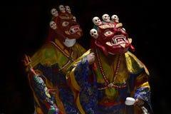 Δύο βουδιστικοί μοναχοί σε μια μπλε παραδοσιακή τήβεννο με ένα κίτρινο περιλαίμιο και μια κόκκινη ξύλινη μάσκα με τους κυνόδοντες Στοκ Εικόνα