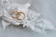 Δύο γαμήλια δαχτυλίδια και γαμήλια ανασκόπηση Στοκ Φωτογραφίες