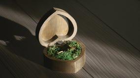 Δύο γαμήλια δαχτυλίδια στο ξύλινο κιβώτιο φιλμ μικρού μήκους