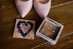Δύο γαμήλια χρυσά δαχτυλίδια στο ξύλινο κιβώτιο Κοντά στα μόνιμα νυφικά ρόδινα παπούτσια Στοκ φωτογραφία με δικαίωμα ελεύθερης χρήσης