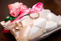 Δύο γαμήλια δαχτυλίδια βρίσκονται στο μαξιλάρι Στοκ Εικόνες