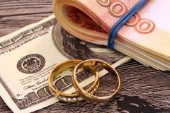 Δύο γαμήλια δαχτυλίδια και χρήματα Στοκ Φωτογραφία