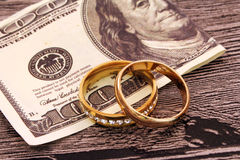 Δύο γαμήλια δαχτυλίδια και χρήματα Στοκ φωτογραφία με δικαίωμα ελεύθερης χρήσης