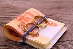 Δύο γαμήλια δαχτυλίδια και χρήματα Στοκ εικόνες με δικαίωμα ελεύθερης χρήσης