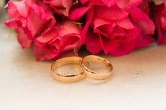Δύο γαμήλια δαχτυλίδια, κόκκινα τριαντάφυλλα Στοκ φωτογραφία με δικαίωμα ελεύθερης χρήσης