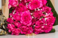 Δύο γαμήλια δαχτυλίδια, κόκκινα τριαντάφυλλα Στοκ Εικόνες