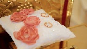 Δύο γαμήλια δαχτυλίδια με το κόκκινο λουλούδι στο υπόβαθρο απόθεμα βίντεο