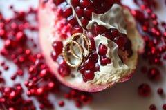 Δύο γαμήλια δαχτυλίδια στο γρανάτη Άσπρος πίνακας φρούτων Στοκ Φωτογραφία