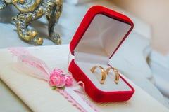 Δύο γαμήλια χρυσά δαχτυλίδια με τα διαμάντια είναι σε ένα κόκκινο κιβώτιο Στοκ εικόνες με δικαίωμα ελεύθερης χρήσης