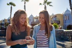 Δύο γελώντας κορίτσια που εξετάζουν το κινητό τηλέφωνο Στοκ Φωτογραφία