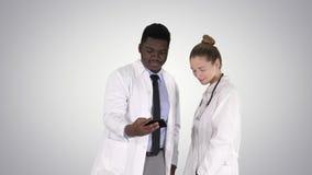 Δύο γιατροί κάνουν selfie χρησιμοποιώντας ένα smartphone και χαμογελώντας στο υπόβαθρο κλίσης φιλμ μικρού μήκους