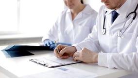 Δύο γιατροί με τις των ακτίνων X τυπωμένες ύλες και τα έγγραφα φιλμ μικρού μήκους