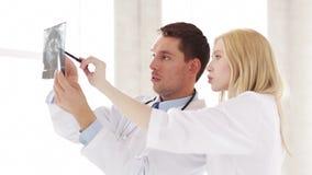 Δύο γιατροί με τις των ακτίνων X τυπωμένες ύλες απόθεμα βίντεο