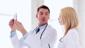 Δύο γιατροί με τις των ακτίνων X τυπωμένες ύλες φιλμ μικρού μήκους
