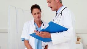 Δύο γιατροί που εξετάζουν την περιοχή αποκομμάτων στο ιατρικό γραφείο απόθεμα βίντεο