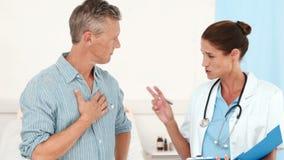 Δύο γιατροί που μιλούν μαζί και που εξετάζουν την περιοχή αποκομμάτων φιλμ μικρού μήκους