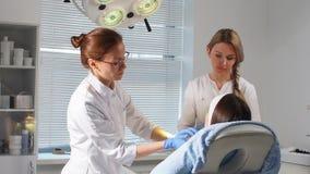 Δύο γιατροί που συμβουλεύονται έναν πελάτη μετά από τη χειρουργική επέμβαση απόθεμα βίντεο