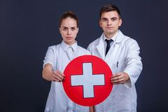 Δύο γιατροί σε ομοιόμορφο, κρατούν ένα ιατρικό σημάδι, ένας άσπρος σταυρός σε έναν κόκκινο κύκλο στοκ φωτογραφίες με δικαίωμα ελεύθερης χρήσης