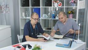 Δύο γιατροί στις κλινικές γραφείων συναντιούνται απόθεμα βίντεο