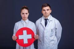 Δύο γιατροί στον άσπρο ομοιόμορφο τύπο και το κορίτσι, στάση και κρατούν ένα ιατρικό σημάδι ένας άσπρος σταυρός σε έναν κόκκινο κ στοκ εικόνες