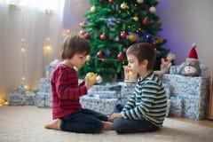 Δύο γλυκά παιδιά, αδελφοί αγοριών, άνοιγμα παρουσιάζουν στα Χριστούγεννα Στοκ φωτογραφία με δικαίωμα ελεύθερης χρήσης