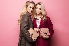 Δύο γλυκές νέες γυναίκες που θέτουν στα συμπαθητικά ενδύματα, παλτό, τσάντα Αδελφές, δίδυμα Φωτογραφία μόδας άνοιξη Στοκ Εικόνες