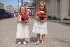 Δύο γοητευτικές αδελφές με τις όμορφες ανθοδέσμες στοκ φωτογραφίες