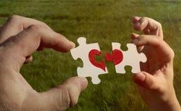 Δύο γρίφοι χαρτονιού με μια χρωματισμένη κόκκινη καρδιά κρατιούνται στα χέρια Στοκ Εικόνες